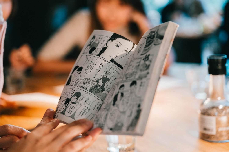 漫画で予習をしながら朝食を注文する人たち